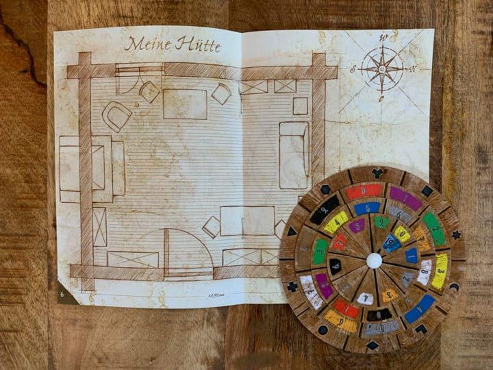 Ein Buch mit dem Lageplan der verlassenen Hütte. Darauf liegt die runde Decodier-Scheibe.