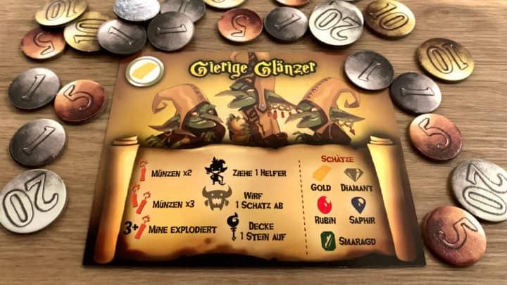 """Eine """"Gierige Glänzer"""" Clan-Karte umgeben von einem Haufen Münzen."""