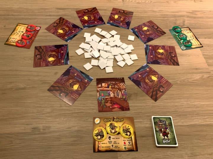 Spielaufbau von Gierige Goblins. Ein Haufen Spielsteine liegt in der Mitte des Tisches. Die Minen und Clan-Karten sind kreisförmig darum angeordnet.