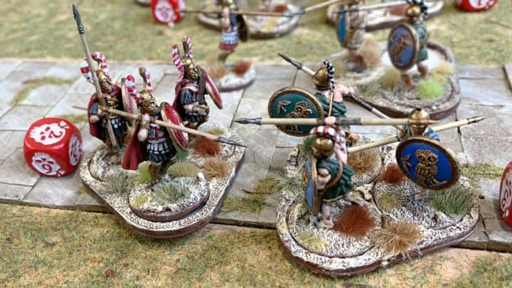 Nahaufnahme von Mortal Gods Figuren. Hopliten aus Sparta und Athen treffen im Nahkampf aufeinander.