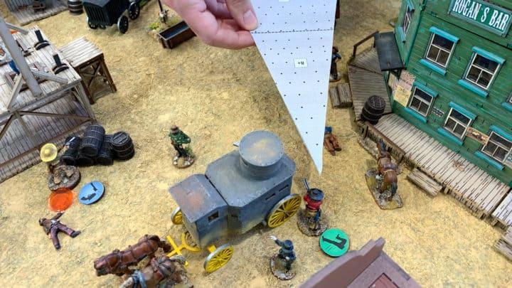 Draufsicht auf den Platz vor dem Saloon. Mit einer dreieckigen Schablone wird die Trefferzone einer Figur angezeigt. Neben anderen Figuren im Bild liegen farbige Spielmarker.