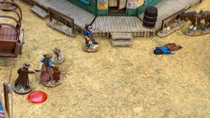 Shootout zwischen Cowboy und Bandit. Der Cowboy versteckt sich hinter Zivilisten. Vor dem Saloon liegt der getroffener Bandit auf dem Boden.