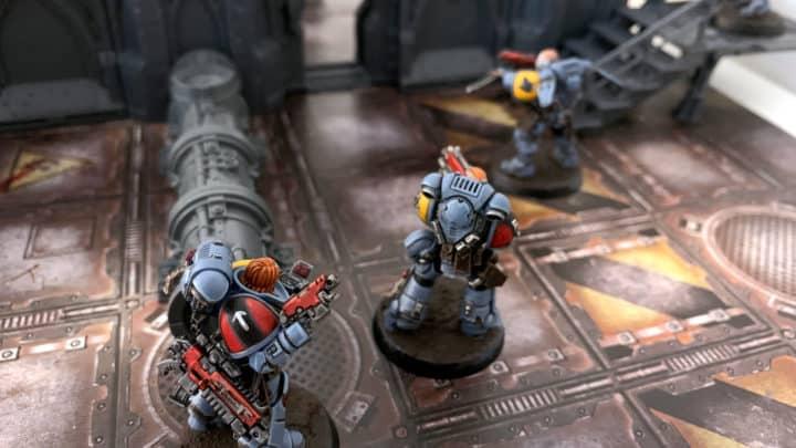Drei Warhammer 40.000 Space Marines auf einer bedruckten Spielmatte. Um sie herum wurde Necromunda Underhive Gelände platziert.