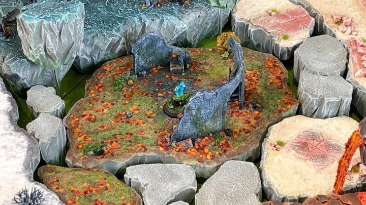 Tabletop-Spieltisch mit schwebenden Inseln und unterschiedlichen Biomen. In der Mitte ein schwebender Feldbrocken im Herbst-Look. An den Seiten sind Winter, Wüste und Lava zu sehen.
