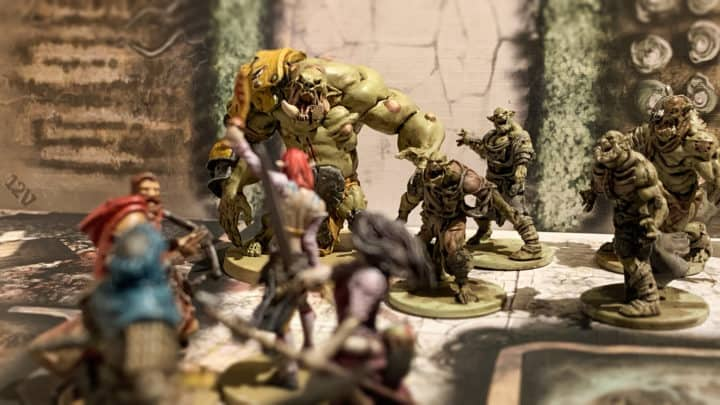 Ein Ausschnitt aus dem kooperativen Spiel Zombicide. Eine Gruppe Überlebender trifft auf untote Orks. Die Modelle stammen aus der Black Plage und Green Horde Box.