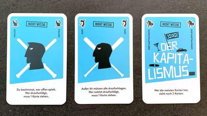 Drei nicht-witzige Spielkarten. Von links nach rechts: Polizei, Nazi, Kapitalismus