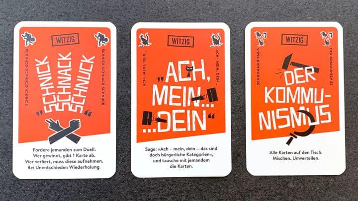 """Drei nicht-witzige Spielkarten. Von links nach rechts: Schnick-Schnack-Schnuck, """"Ach - mein, dein"""" und Kommunismus."""