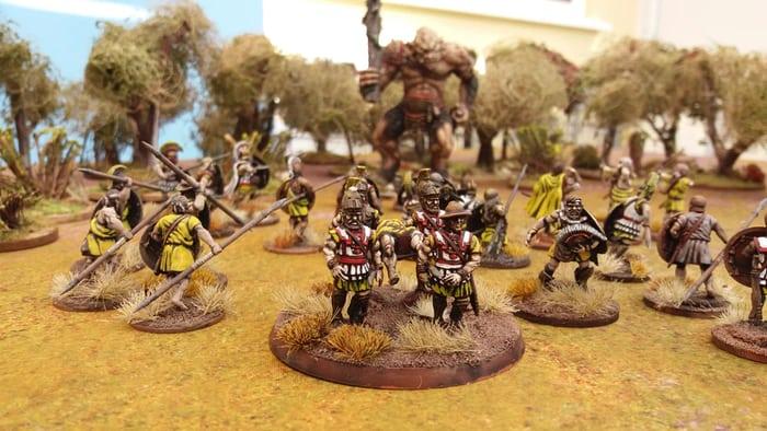 Griechen tragen einen Helden auf seinem Schild vom Schlachtfeld. Im Hintergrund kämpfen Hopliten und Bogenschützen gegen einen Zyklopen.