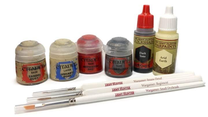 Farben und Pinsel zum Bemalen von Miniaturen. Im Vordergrund liegen drei Army Painter Pinsel, im Hintergrund sind diverse Citadel und Army Painter Farben zu sehen.