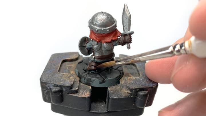 Die Grundfarbe wird mit einem Pinsel auf die Figur aufgetragen.