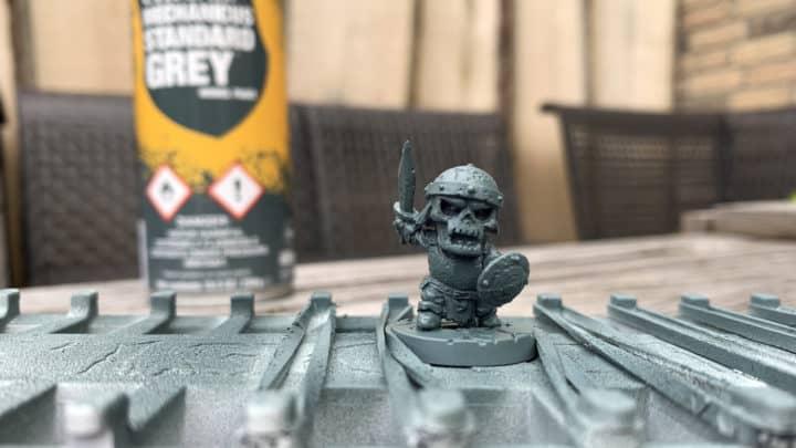 Eine mit grauer Farbe grundierte Miniatur. Im Hintergrund steht eine Dose Citadel Mechanicus Standard Grey.