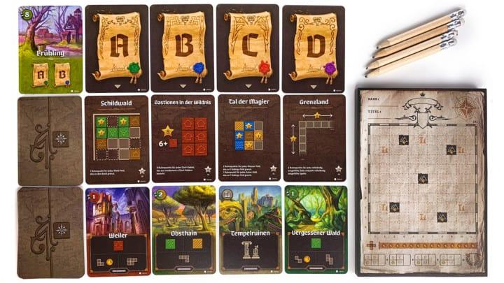 Das Spielfeld von Der Kartograph. In der oberen Reihe liegen Karten für die Jahreszeit und Zielvorhaben. In der mittleren Reihe liegen die Wertungskarten und in der unteren Reihe Erkundungskarten.